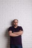 Stående av en man, armar korsade händer, mot den vita väggen Arkivbild
