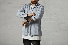 Stående av en man i den vit t-skjortan och grov bomullstvill Arkivfoto