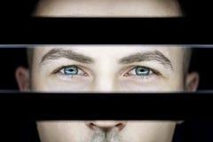 Stående av en man i mörker i ljus av lampor Atmosfäriskt konstfoto av en grabb med gröna ögon Framsidan för man` s på andra sidan Fotografering för Bildbyråer