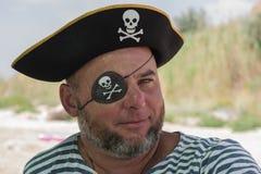 Stående av en man i en piratkopieradräkt på stranden Arkivfoto