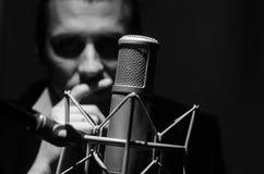 Stående av en man med studiomikrofonen Arkivbild
