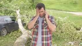 Stående av en man med en telefon, följderna av en naturkatastrof Arkivbild
