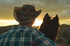 Stående av en man och en hund i baksidan Grabb och hund på solnedgången royaltyfri fotografi
