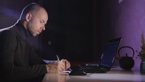 Stående av en man på hans bärbar dator på natten med en framsida av koncentration arkivfilmer