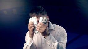 Stående av en man som döljer hans framsida bak en fan av pengar som räknar dem stock video