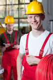 Stående av en man som rymmer en rulle av röd kabel arkivfoto