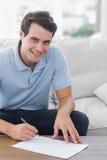 Stående av en manhandstil på ett papper, medan han sitts på en soffa fotografering för bildbyråer