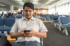 Stående av en mellersta ålderman som sitter på bänk och att använda den smarta telefonen, leende med blick på mobiltelefonen i en fotografering för bildbyråer