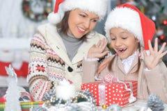 Stående av en moder och en dotter med julgåvan royaltyfri fotografi
