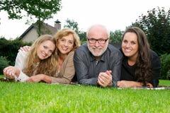 Stående av en moder och en fader som ler samman med två äldre döttrar Arkivbild