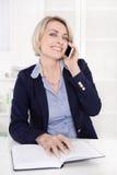 Stående av en mogen eller hög affärskvinna som flörtar på mobil Royaltyfria Bilder