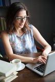 Stående av en mogen kvinna i glasögon som skriver på bärbara datorn arkivfoton