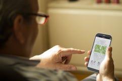 Stående av en mogen man som ser online-marketingin en mobil pho Fotografering för Bildbyråer