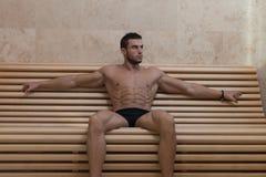 Stående av en muskulös man som kopplar av i bastu royaltyfria foton