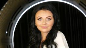 Stående av en mycket härlig blåögd kvinnamodell med långt svart hår och härliga aftonsminket som framme poserar av stock video
