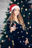 Stående av en mycket trendig, kall och elegant festlig ung kvinna nära en julgran med exponeringsglas royaltyfria bilder