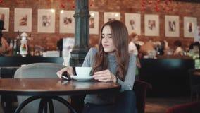 Stående av en nätt flicka i ett kafé flickan gör selfie på kamerasmartphonen och dricker kaffe arkivfilmer