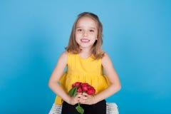 Stående av en nätt flicka med röda rädisor för nya grönsaker royaltyfri fotografi