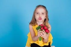 Stående av en nätt flicka med röda rädisor för nya grönsaker royaltyfri bild