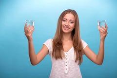 Stående av en nätt flicka som rymmer två exponeringsglas med Arkivfoton