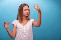Stående av en nätt flicka som rymmer två exponeringsglas med Arkivbild