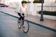 Stående av en nätt kvinna på cykeln i staden royaltyfri foto