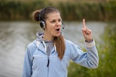 Stående av en nätt le kundtjänstoperatör som bär en hörlurar med mikrofon fotografering för bildbyråer