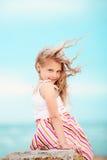 Stående av en nätt liten flicka med att vinka i de långa mumlen för vind Arkivbild
