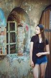 Stående av en nätt mörker-haired flicka på bakgrunden av en gammal byggnad retro stil royaltyfria foton