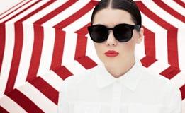 Stående av en nätt ung kvinna i den vit chemisen och solglasögon med ljusa målade kanter royaltyfri foto