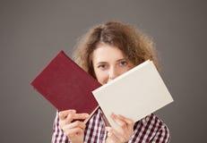 Stående av en nätt ung kvinna med två böcker royaltyfri fotografi