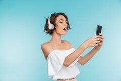 Stående av en nätt ung kvinna som lyssnar till musik royaltyfri foto