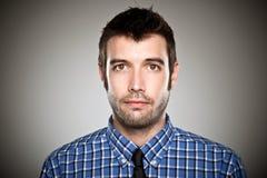 Stående av en normal pojke över grå bakgrund. Arkivfoton