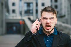 Stående av en ond affärsman som ropar till mobiltelefonen mot bakgrunden av det moderna stads- landskapet arkivbild