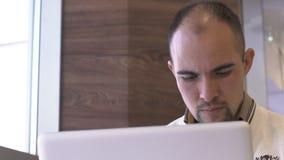 Stående av en orakad skallig man som arbetar för en bärbar dator stock video
