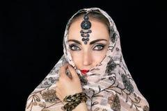 Stående av en orientalisk ung kvinna i en halsduk med en prydnad och juvlar på en svart bakgrund fotografering för bildbyråer