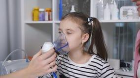 Stående av en pediatrisk kvinna och lite flickan med en inandningmaskering från en nebulizer i sjukhuset lager videofilmer