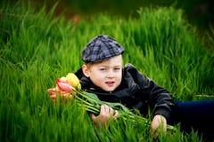 Stående av en pojke, ett barn som rymmer en bukett av blommor Royaltyfri Bild