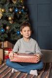 Stående av en pojke med en gåvaask i hans händer nära julträdet för nytt år arkivfoton