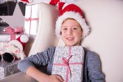 Stående av en pojke med gåvan och julhatten Royaltyfri Foto