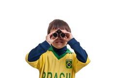 Stående av en härlig pojke med kikare över vitbakgrund Arkivfoto
