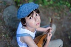 Stående av en pojke med en mandolin Arkivbilder