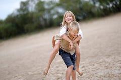 Stående av en pojke och en flicka på stranden Arkivbild