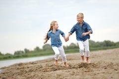 Stående av en pojke och en flicka på stranden Arkivfoton