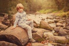 Stående av en pojke på en bakgrund av naturen Barnet sitter på vaggar vid floden royaltyfria foton