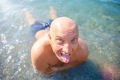 Stående av en positiv man som simmar i havet Arkivbild