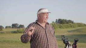 Stående av en säker lyckad mogen man med ett golfklubbanseende på en golfbana i bra soligt väder sport lager videofilmer