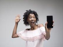 Stående av en säker tillfällig afro flicka som visar mobiltelefonen för tom skärm royaltyfria bilder
