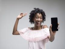 Stående av en säker tillfällig afro flicka som visar mobiltelefonen för tom skärm fotografering för bildbyråer