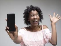 Stående av en säker tillfällig afro flicka som visar mobiltelefonen för tom skärm arkivbild
